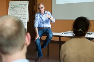 """Praxisdozent Dr. Johannes Merck, Direktor des Bereichs Corporate Responsibility der der Otto Group erläutert den Begriff der """"Schadschöpfung"""" in M2."""